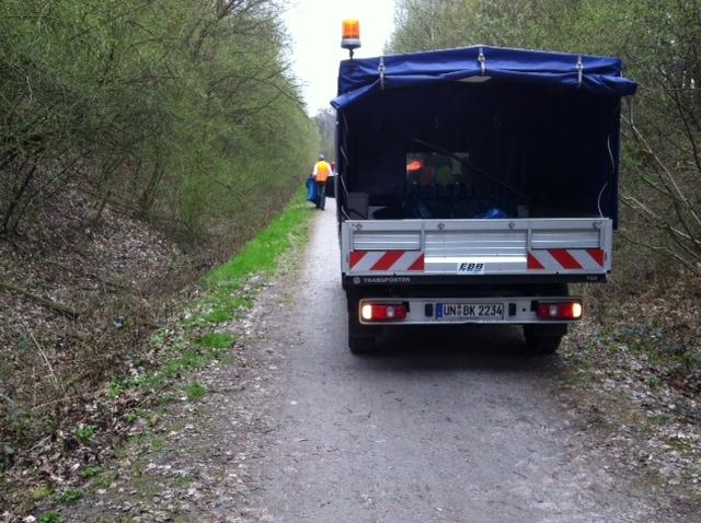 Mitarbeiter sammeln Müll an der Kuhbachtrasse.