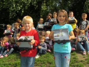 Stolz präsentieren die Kinder der Kitas am Grünen Weg und der St. Michael-Gemeinde ihre selbst gebastelten Sammel-Loren.