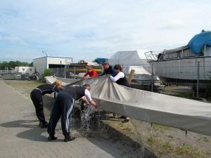 Nach einem Regen ist es gar nicht so einfach, die Plane vom Drachenboot herunterzunehmen, ohne selbst nass zu werden.