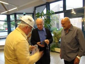 Kohle aus Bergkamen überreichen Peter Schedalke (l.) vom IGBCE/REVAG-Geschichtsarbeitskreis und der Vorsitzende von Arbeit und Leben, Heint Mathwig (r.), Eugen Drewermann vor Beginn seines Vortrags.