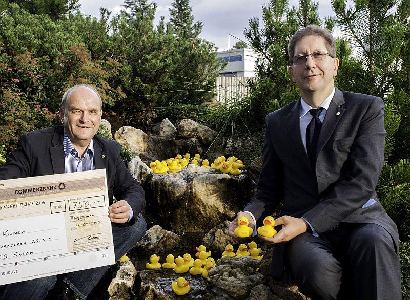 Dr. Stefan Klatt (r.) und Hans Determann, Präsident des Rotary Clubs Kamen, präsentieren einige der 150 Enten, mit deren Erwerb Bayer die Kamener Grundschulen unterstützt.