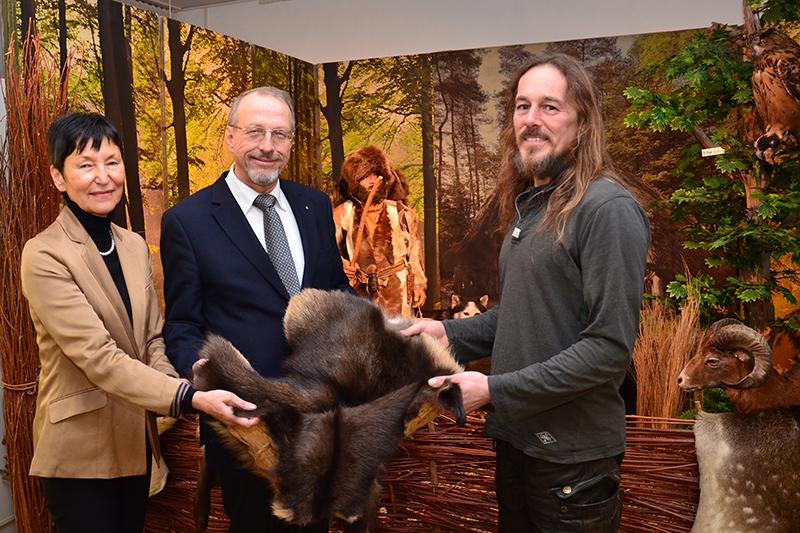 Ausstellungseröffnung der anderen Art: Ötzi schaut zu, wie Barbara Strobel (l.), Bürgermeister Roland Schäfer und Henning Fenner (r.) Hand an das Fell legen.