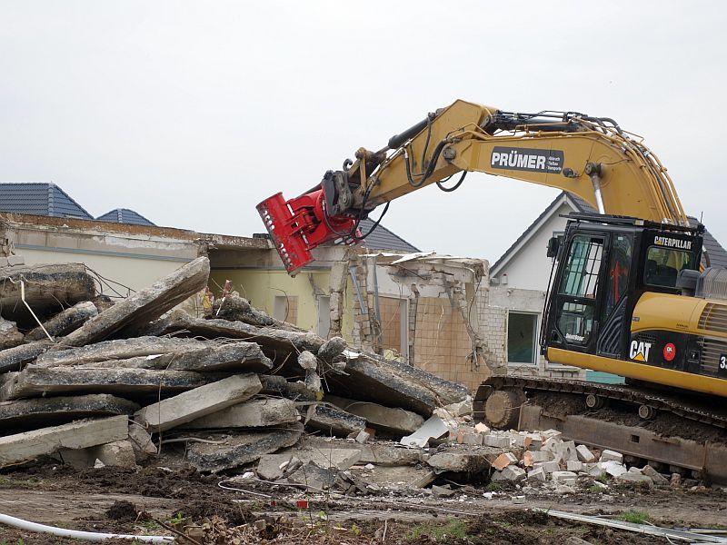 Ein Abbruchbagger macht jetzt das ehemalige Gesundheitshaus von Grimberg 3/4 platt.