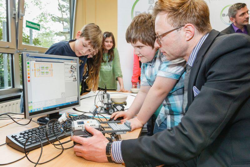 Schüler der Realschule Oberaden erläutern Stiftungsvorstand Thimo V. Schmitt-Lord (r.) die Programmierung der Roboter.