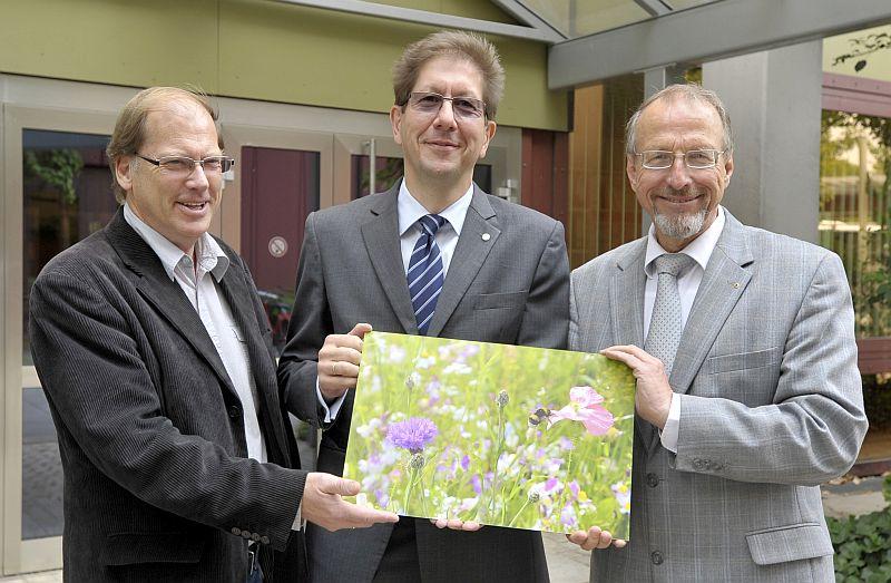 Ein Foto mit blühenden Wildblumen übergab Standortleiter Dr. Stefan Klatt (Mitte) als dekoratives Symbol der Bayer-Saatgutspende an Bürgermeister Roland Schäfer (r.) und Hans Irmisch, Stadt Bergkamen. Foto: Bayer