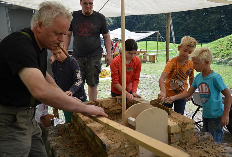 Bauen wie die Römer: Ein echter römischer Backofen entsteht neben der Holz-Erde-Mauer.