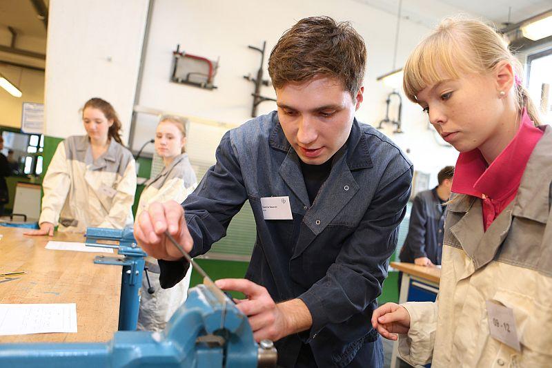 Unterricht der besonderen Art: Bayer-Auszubildende helfen Schülerinnen und Schülern beim Anfertigen einfacher Werkstücke aus Metall.