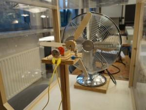 Ein kleines Windrad aus Holz wird im Windkanal getestet.