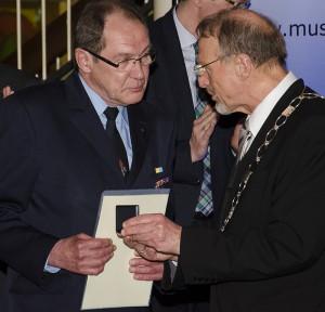 Bürgermeister Roland Schäfer überreicht die Ehrenmedaille.