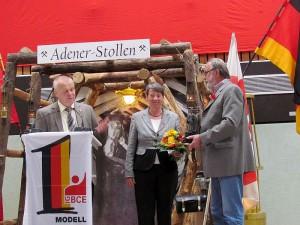 Mario Unger (l.) und Willi Null überreichen der Ministerin einen Blumenstrauß und ein Barbara-Figur aus Kohle.