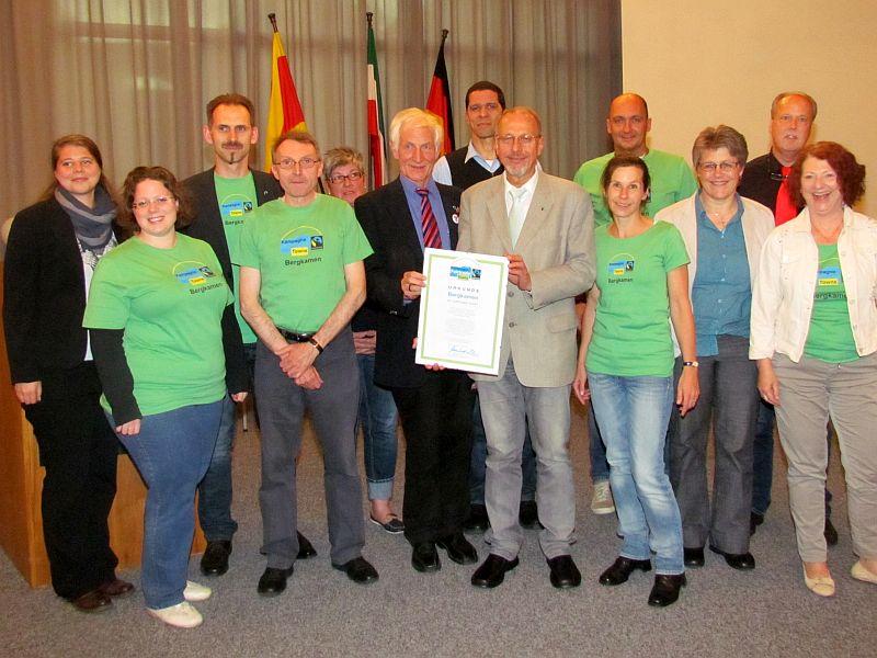 Fairtrade-Ehrenbotschafter Manfred Holz (dunkler Anzug) übergibt die Ernennungsurkunde an Bürgermeister Roland Schäfer. Mit auf dem Foto die Mitglieder des Fairtrade-Lenkungskreises.