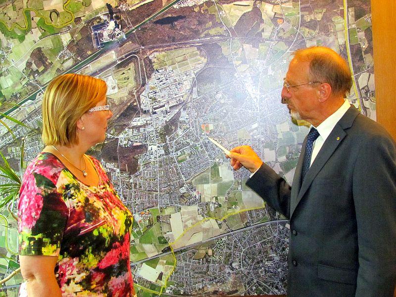 Christine Busch und Roland Schäfer zeigen auf einer Karte während der Pressekonferenz die möglichen Standorte für mögliche Asylbewerberunterkünfte.