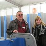 Lena Kärger und Andreas Kleff erläutern die Einrichtungen des Sanitärzelts mit Waschbecken, Duschkabinen und Toiletten.