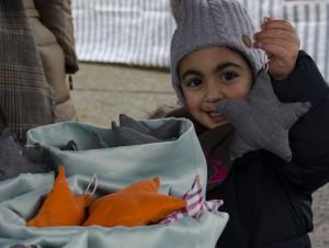 Die kleine Ela zeigt stolz den Weihnachtsbaumschmuck, den Flüchtlingsfrauen selbst genäht haben.