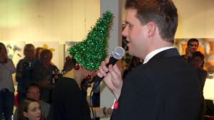 """Gab sein beeindruckendes gesangliches Debut beim """"Swing in den Heiligabend: Jan Schmitt, im Hintergrund Sandra Horn mit ihrer grünen Weihnachtsbaum-Perücke"""
