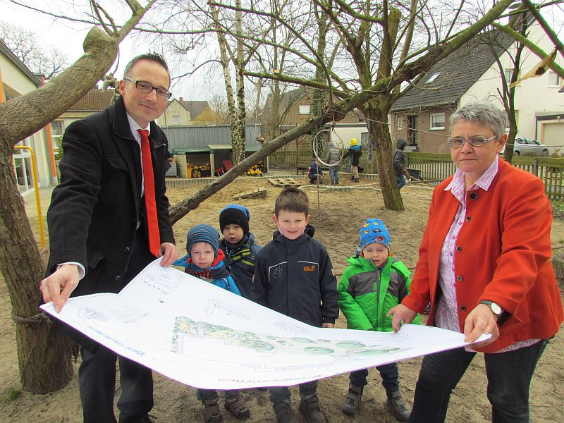 Die Leiterin des Familienzentrums Büscherstiftung Iris Hiepe zeigt mit einigen Kindern Michael Krause den Plan für die naturnahe Neugestaltung des Außengeländes.