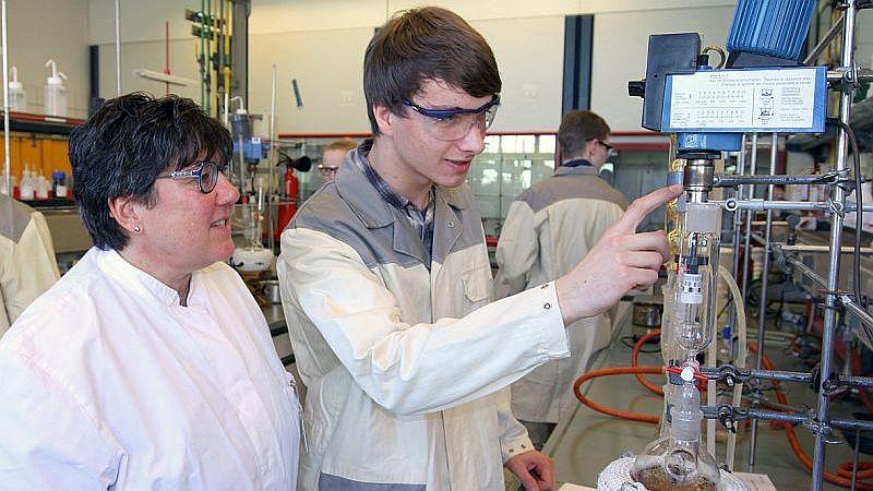 Linus Busse, Teilnehmer der Internationalen Chemieolympiade, erläutert der Landesbeauftragten Birgit Vieler die Besonderheiten einer Apparatur für die Wirkstoff-Synthese.