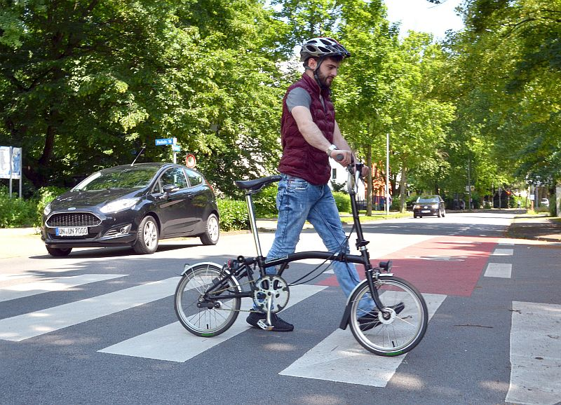 Bildzeile: So ist es richtig: Kreis-Auszubildender Ömer Temur schiebt sein Fahrrad über den Zebrastreifen. Foto: B. Kalle – Kreis Unna