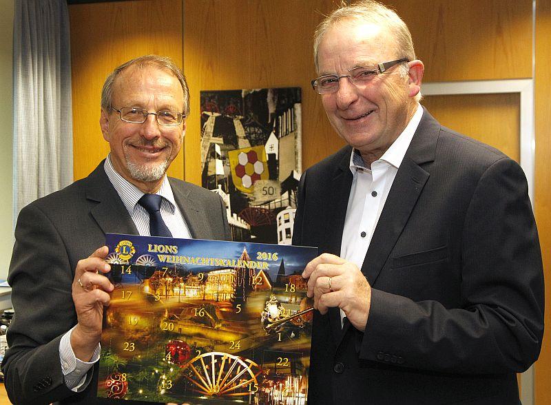 Bürgermeister Roland Schäfer und Lionspräsident Reinhard Middendorf mit dem diesjährigen Weihnachtskalender dse Lionsclubs BergKamen