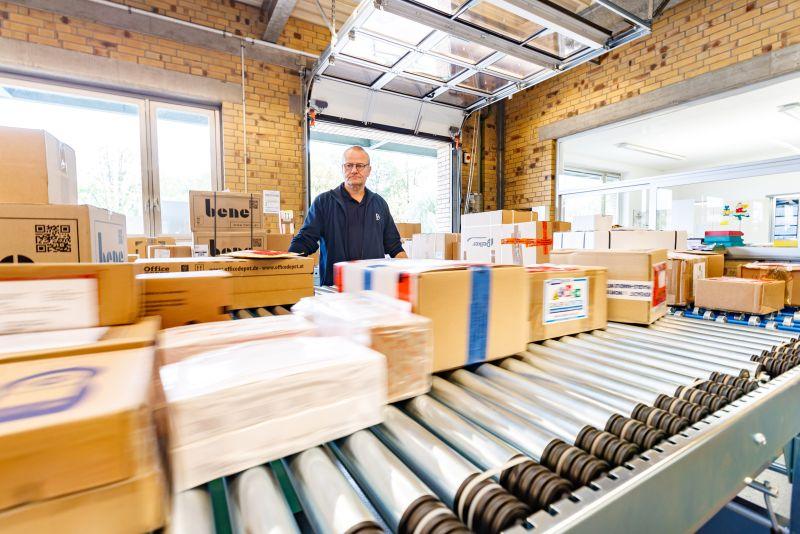 Detlev Gloger demonstriert: Die Bänder sind mit leichtgängigen Rollen und elektronischem Antrieb ausgestattet, so dass das Verteilen der Pakete nur noch minimalen Kraftaufwand erfordert. Foto: Bayer