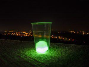 Getränkewürffel als Lichtkunst vor nächtlicher Kulisse.