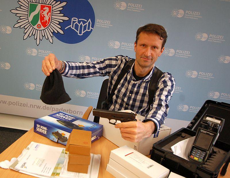 Kriminalhauptkommissar Jürgen Tillmann zeigt neben sichergestellten Beutestücken die Tatwaffe und Mütze des mutmaßlichen Räubers.