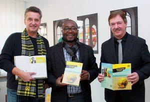 Buchautor Uwe Schedlbauer (l.) spendete dem Flüchtlingsbeauftragten Joel Zombou (m.) und Superintendent Hans-Martin Böcker (r.) druckfrische BVB-Bücher