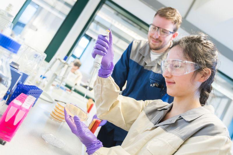 Unter Anleitung von Bayer-Azubi Hendrik Tölle führt Tabea Marx eine Lebendzellzahlbestimmung auf einer Agarplatte durch. Foto: Bayer AG