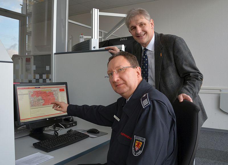 Jens Bongers, Chef der Kreis-Rettungsleitstelle des Kreises Unna (links), zeigt Landrat Michael Makiolla, wie eine Warnmeldung in die App NINA eingespeist wird. Foto: Birgit Kalle – Kreis Unna