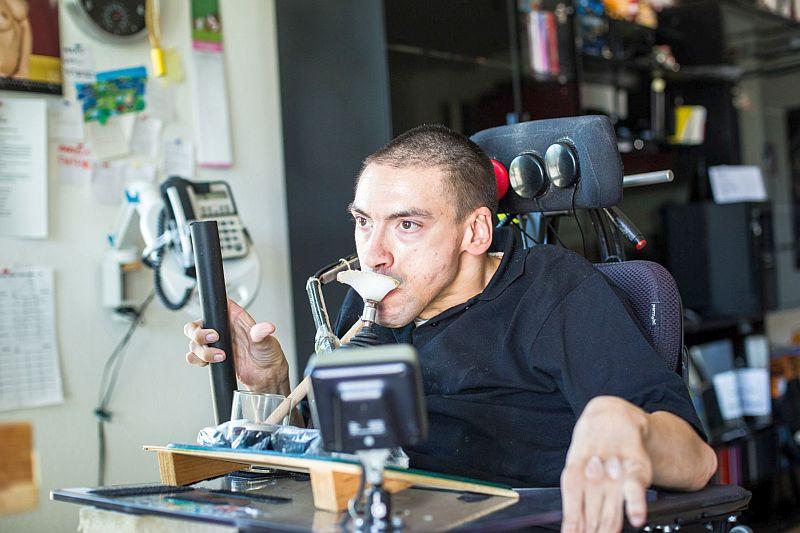 Im Apartmenthaus in Bochum für Menschen mit und ohne Behinderung: Mithilfe eines Holzstabs bedient Marc Szymkowiak die PC-Tastatur.  Foto: LWL/Steffen